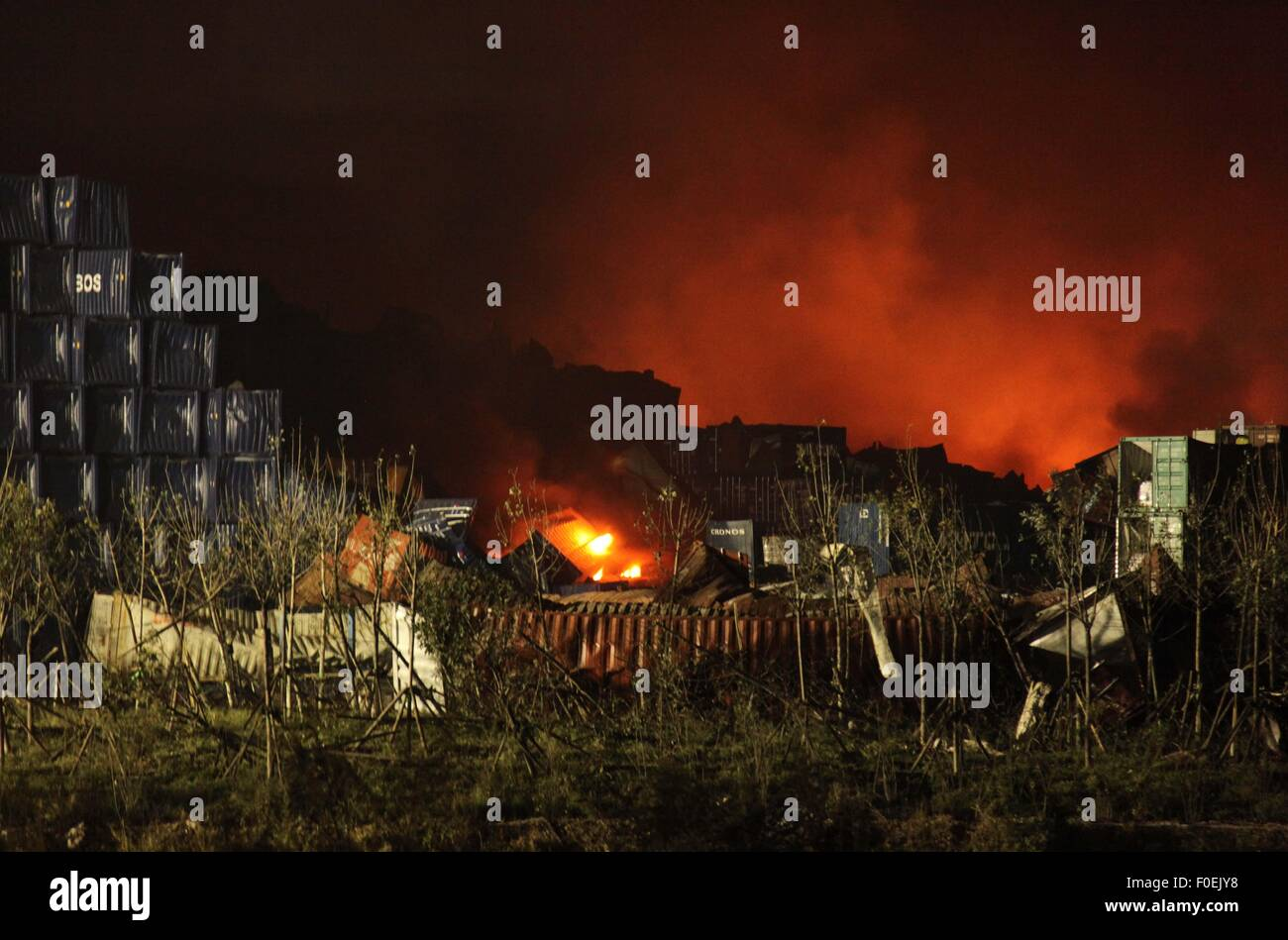 Tianjin, China. 14th Aug, 2015. Flames are seen at the core area of explosion site to in Tianjin, north China, Aug. - Stock Image