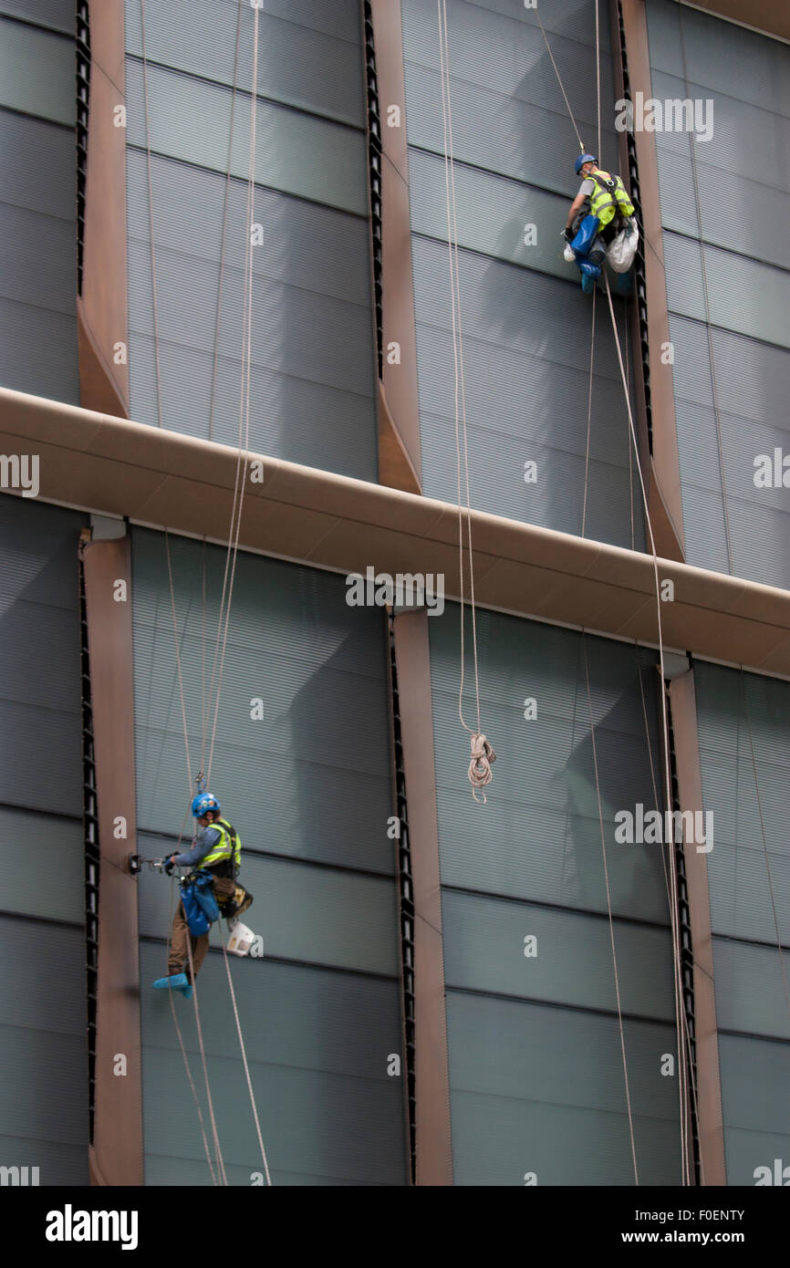 Roped building workers fixing facade to Bloomberg building Cheapside London - Stock Image