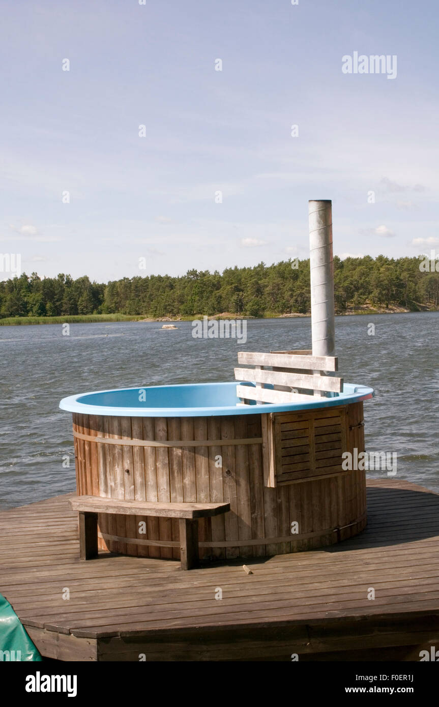 hot tub tubs hottub hottubs outdoor outside sweden swedish lake on a lakes water warm heating specific heat capacity - Stock Image