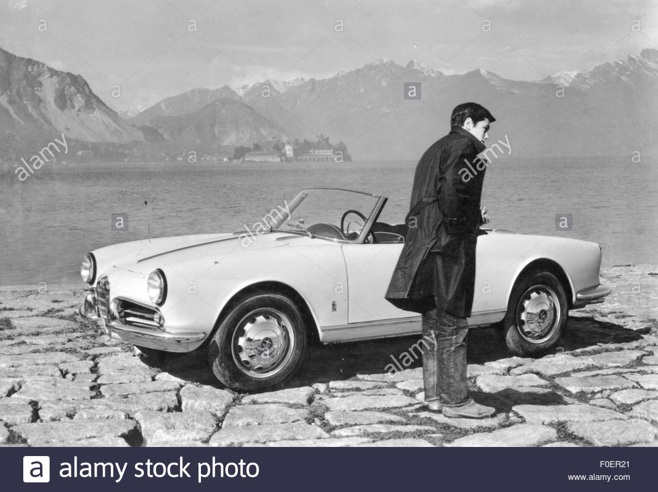 Delon, Alain, * 8.11.1935, French actor, full length, standing besides an Alfa Romeo, Lago Maggiore, 1950s, Additional - Stock Image