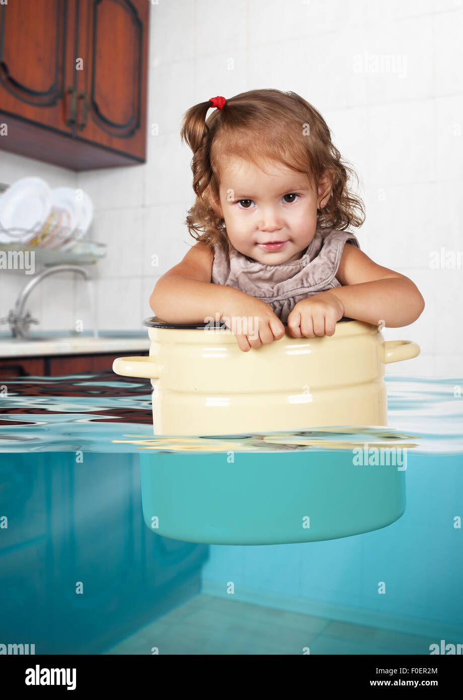 Funny little kid swim in pan in the flooded kitchen, rowdy creative concept - Stock Image