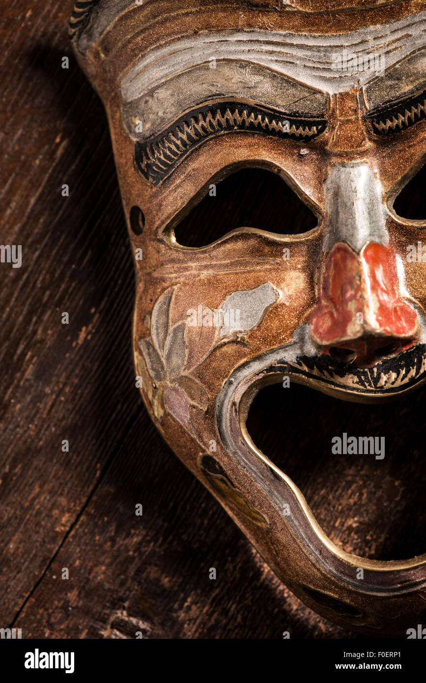 Comedy mask lying on wooden background. Still life showing happiness and positive expression through an object. - Stock Image