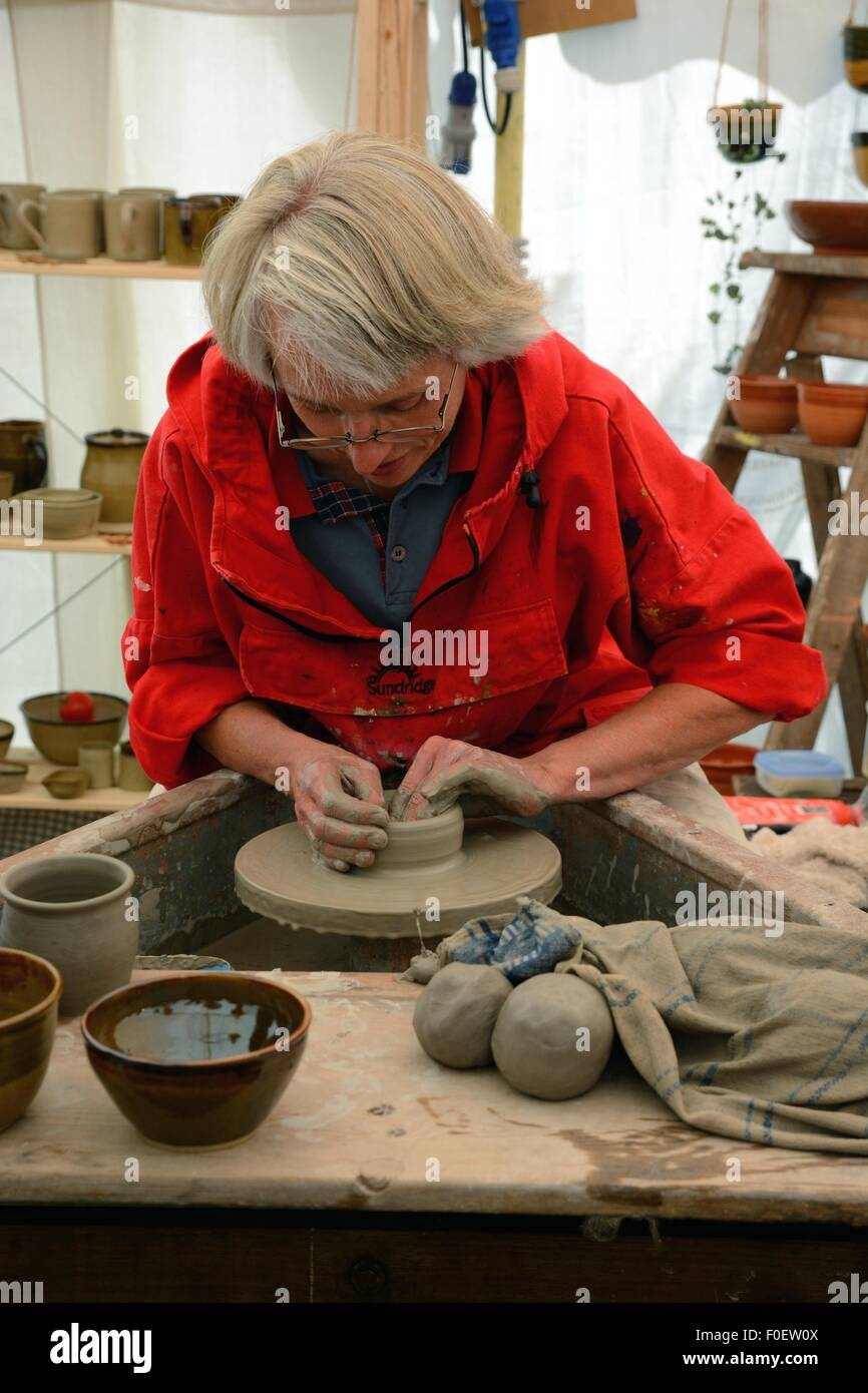 A potter demonstrates her skills with a potters wheel at a country fair. - Stock Image