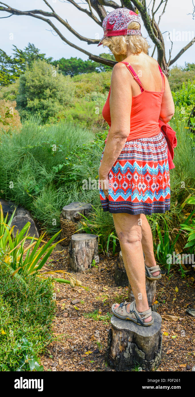Middle aged lady walking on stepping stones in a park. - Stock Image