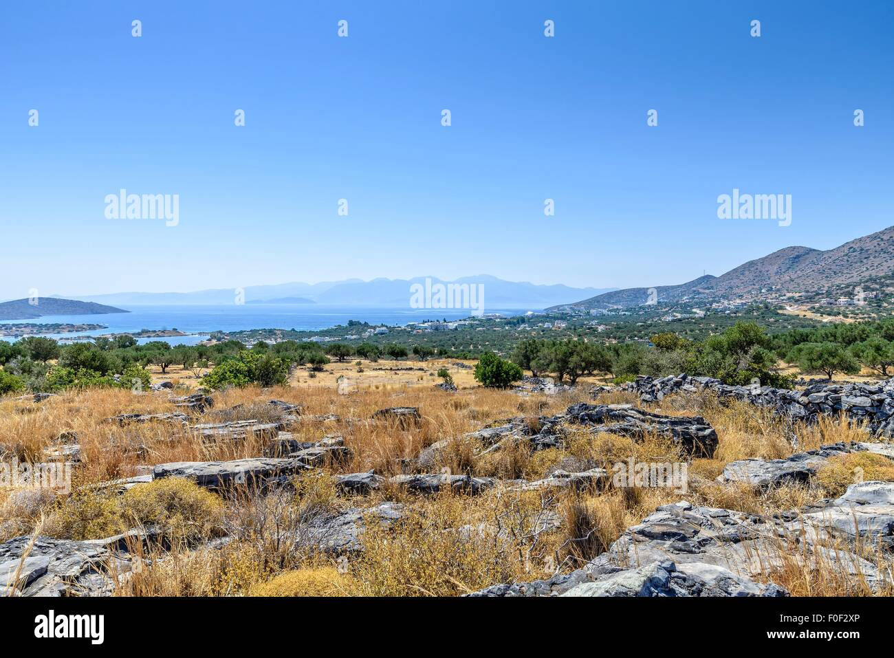 Scrub area looking towards the sea and distant hills with rocks in the foreground. - Stock Image