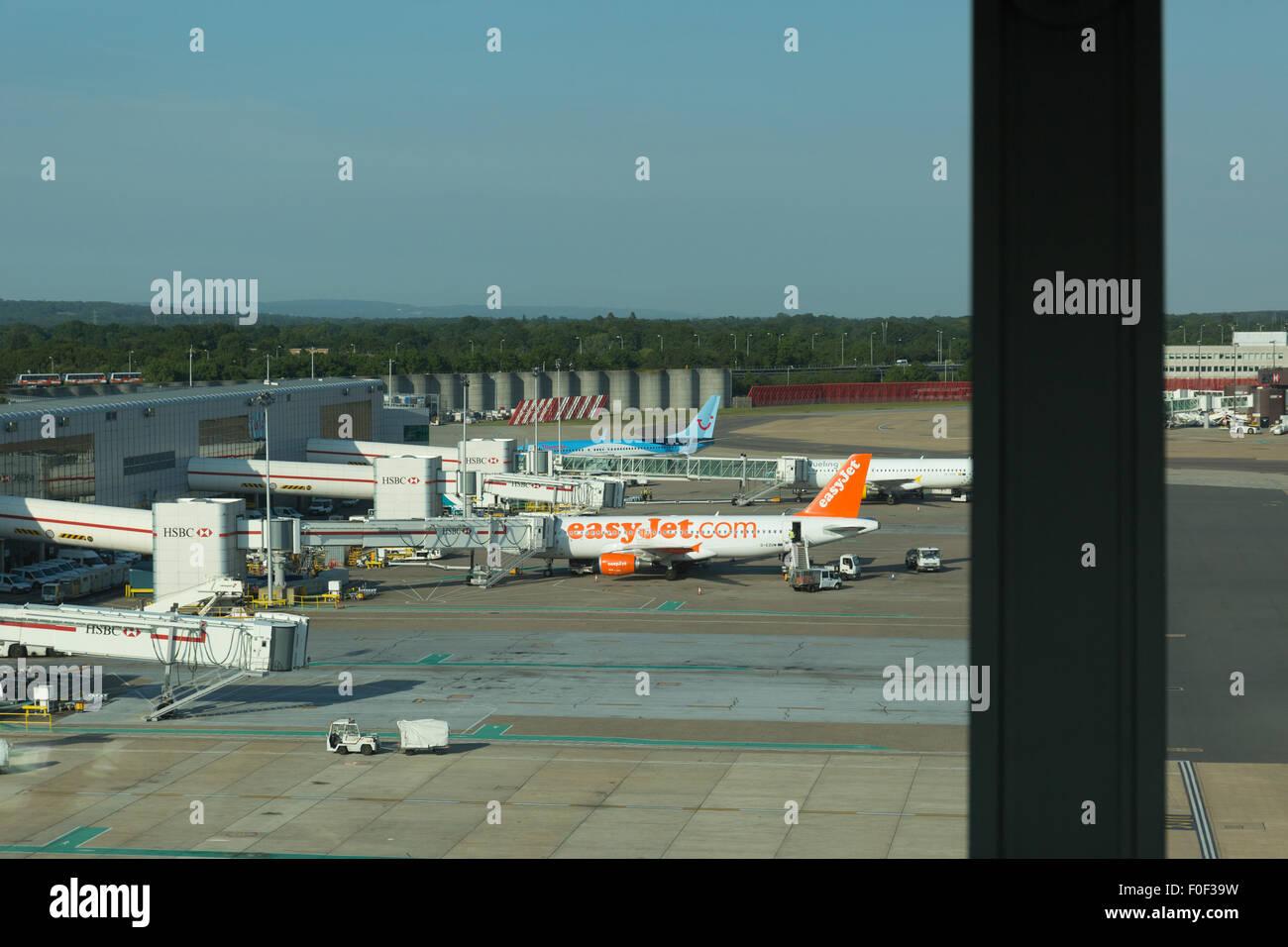 Gatwick airport apron with Easyjet plane and HSBC jet bridge - Stock Image