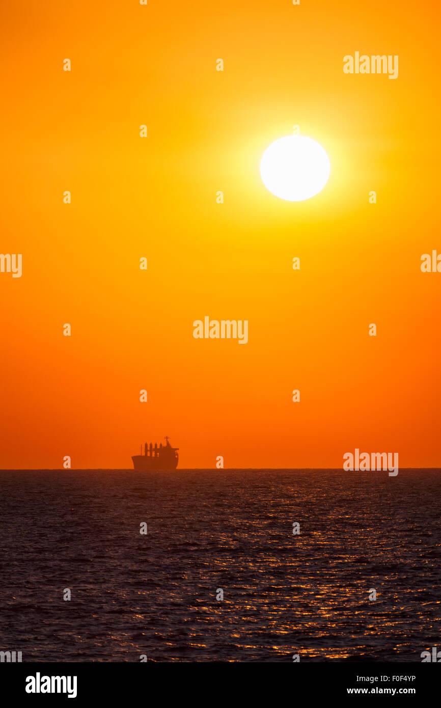 sea sunrise anchored ship - Stock Image