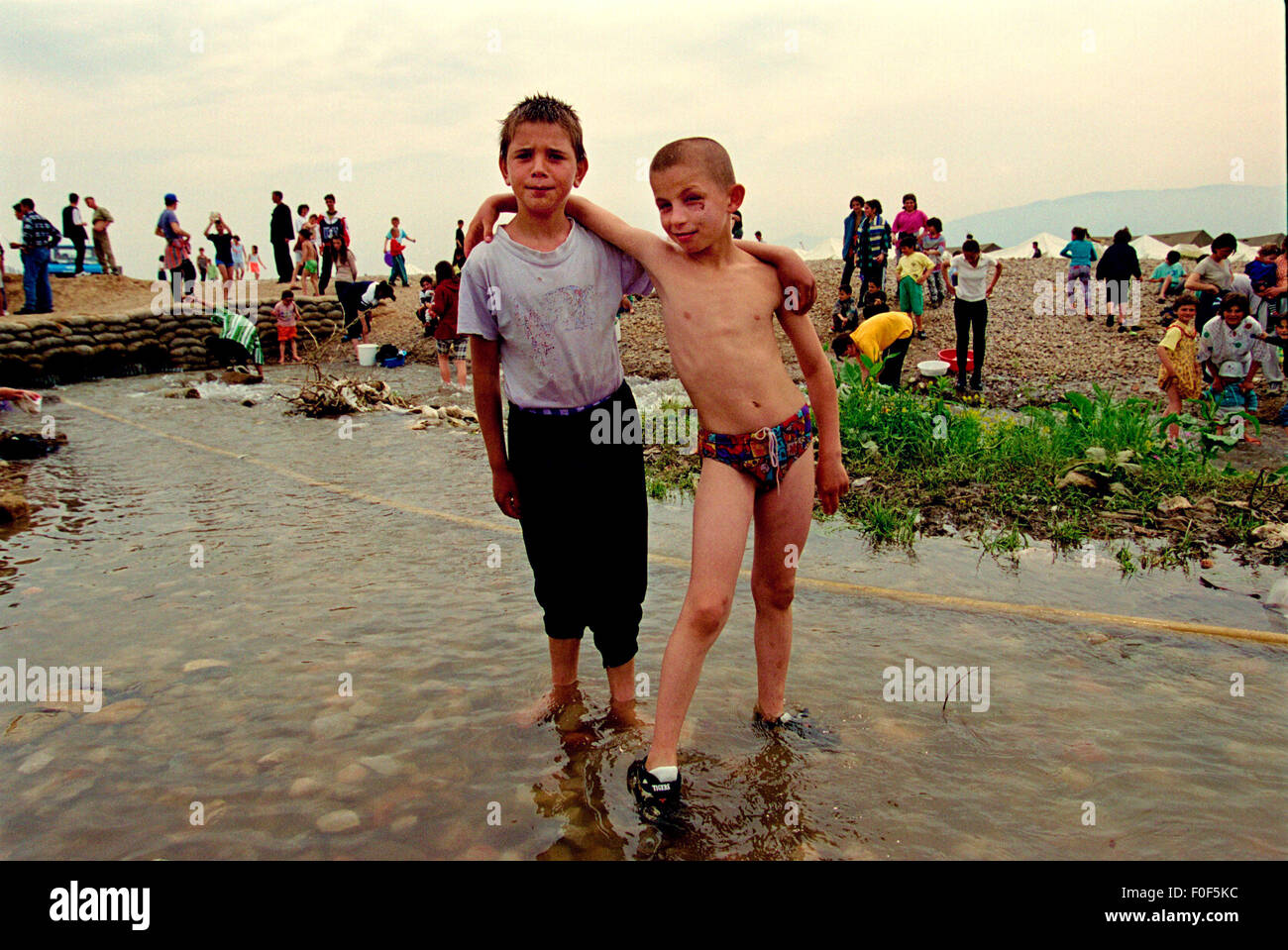 Kosovan refugees at camp Strankovic Macedonia 1999 , to young boys play in the stream that runs through the camp - Stock Image
