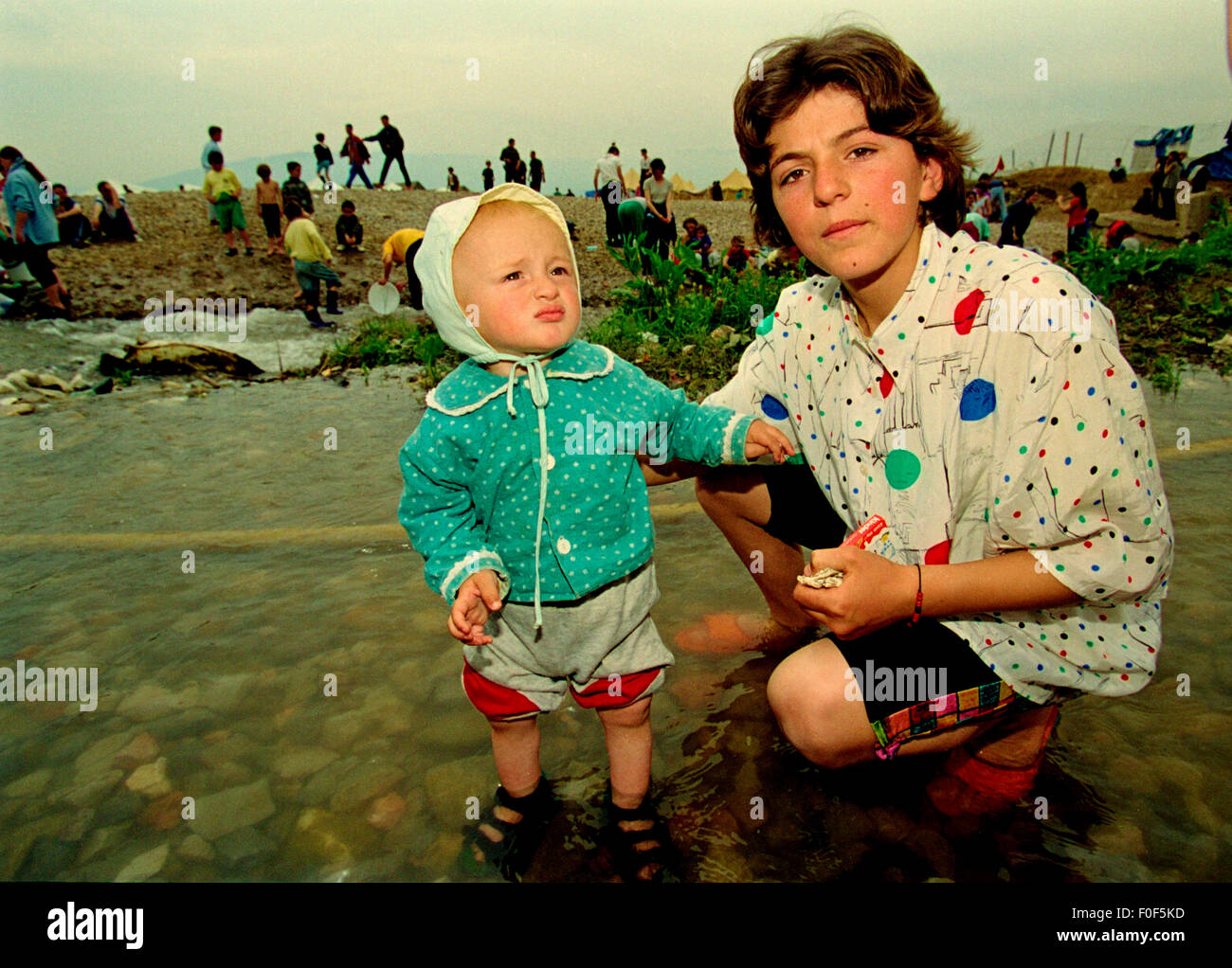 Kosovan refugees at camp Strankovic Macedonia 1999 , a baby stands in the stream that passes through the camp were - Stock Image