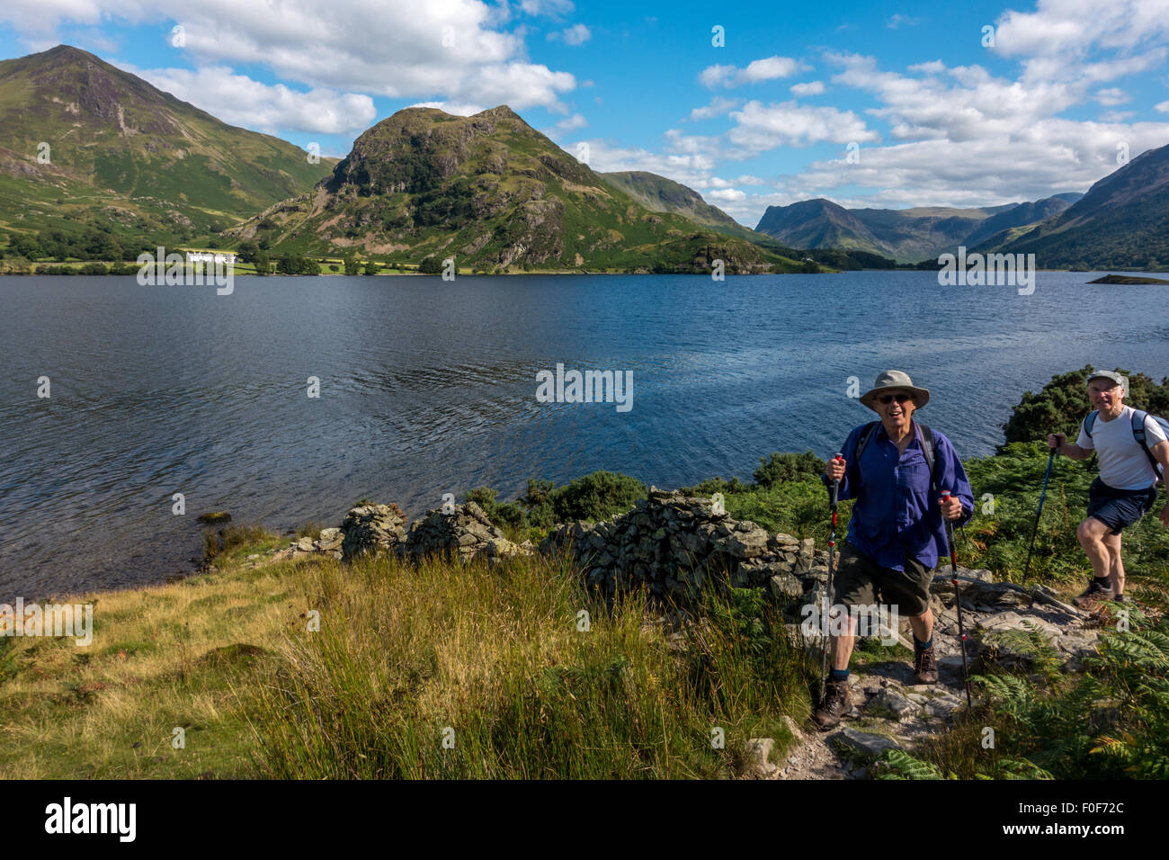 Seniors lifestyle: Two people returning from a walk along the beautiful western shore of Crummock Water, English - Stock Image