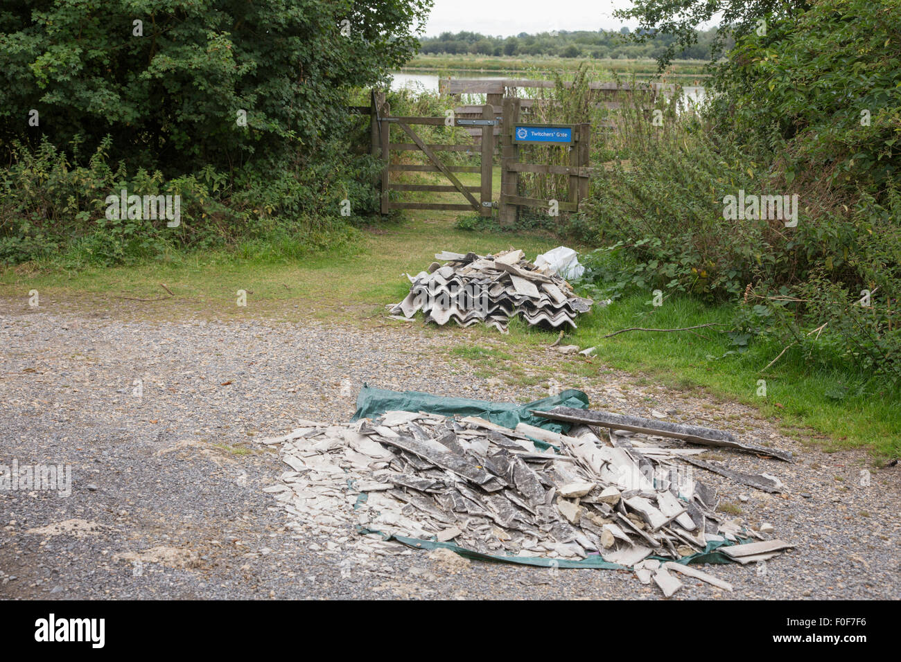Fly-tipping containing Asbestos next to the entrance of a nature reserve, Gloucestershire, England, UK - Stock Image