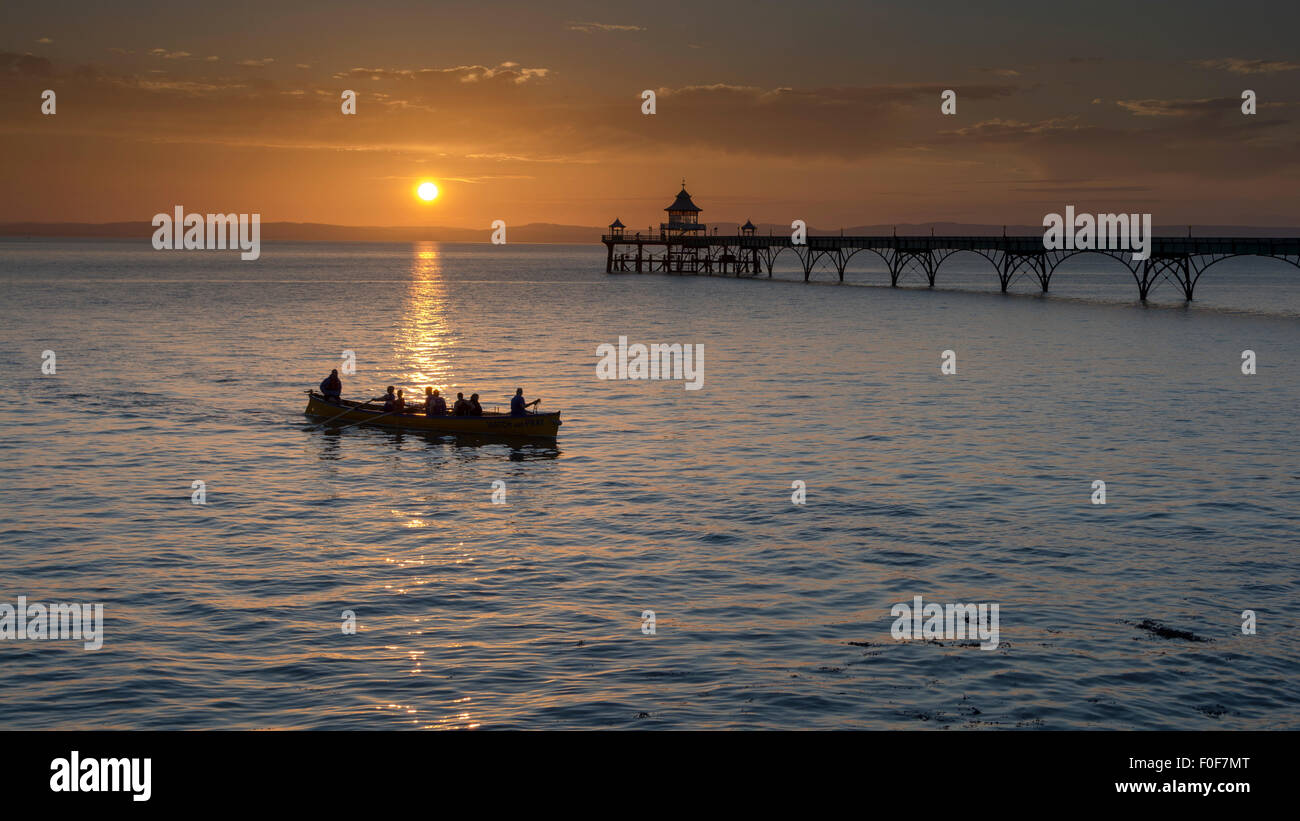 Rowers coming in as the sun sets at the west facing and elegant Clevedon Pier in North Somerset, England, UK - Stock Image
