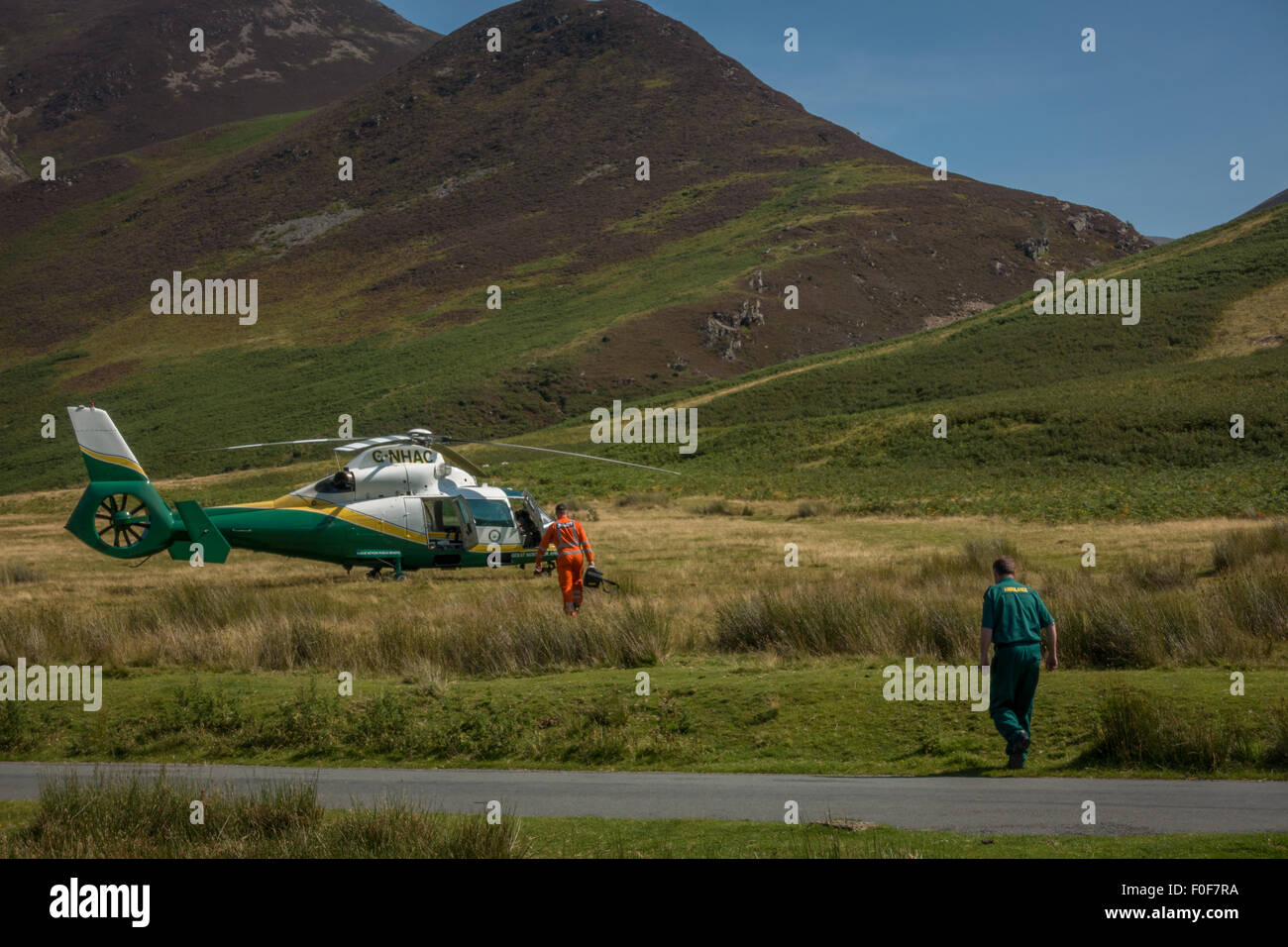 Great North Air Ambulance carrying equipment to the helicopter - on call in Buttermere, Cumbria. - Stock Image