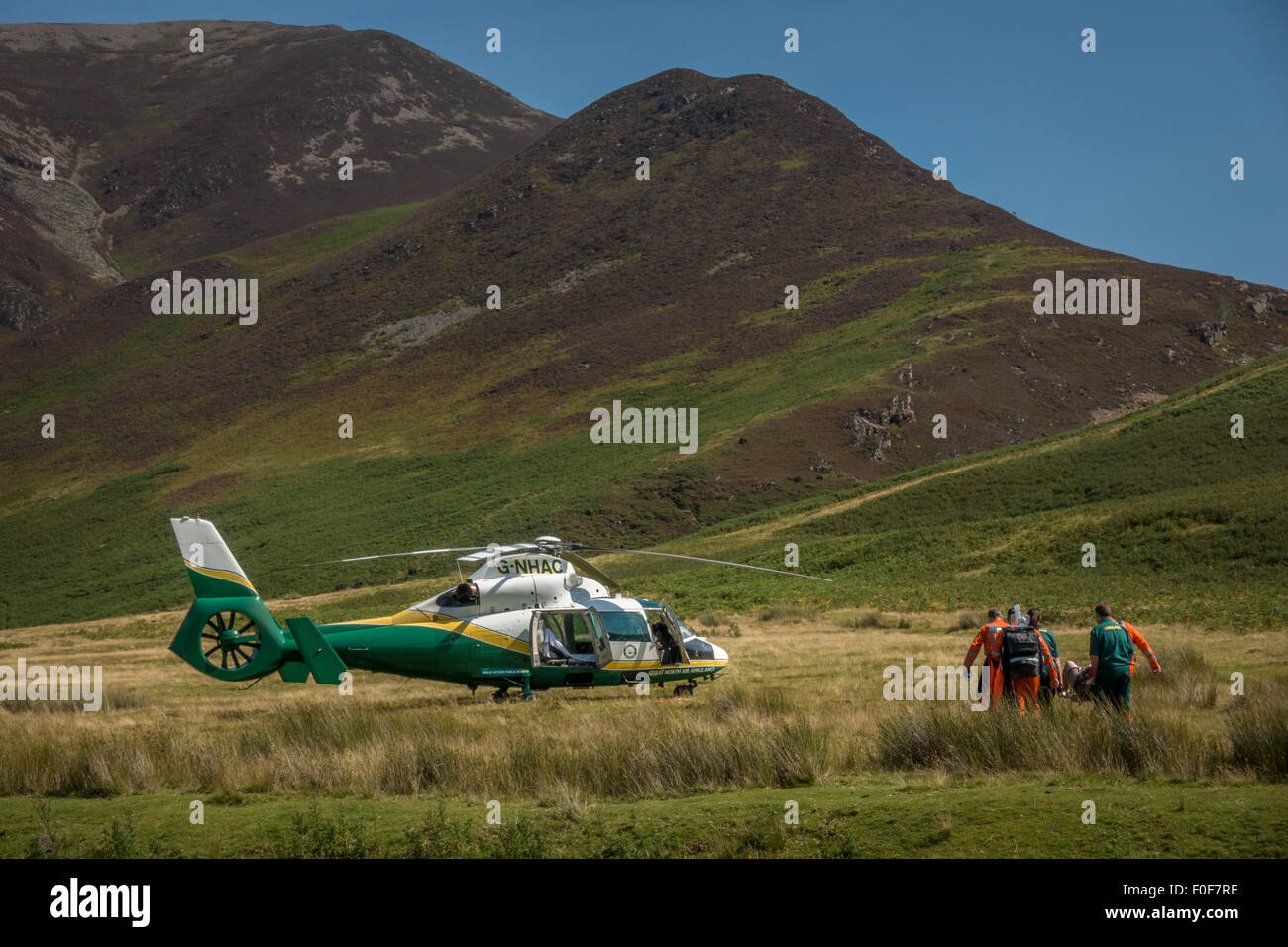 Great North Air Ambulance carrying a patient to the helicopter - on call in Buttermere, Cumbria. - Stock Image
