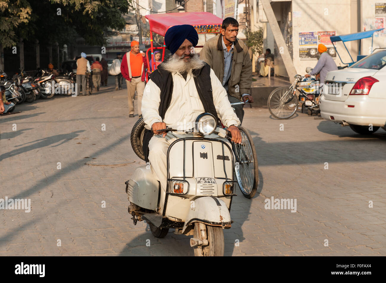 Amritsar, Punjab, India.Elderly Sikh man with flowing white moustache riding a Bajaj Vespa motor scooter wearing Stock Photo