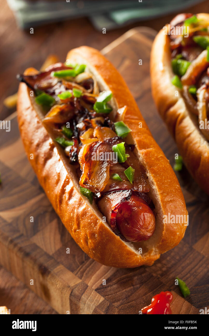 Homemade Bacon Wrapped Hot Dogs with Onions and Peppers - Stock Image