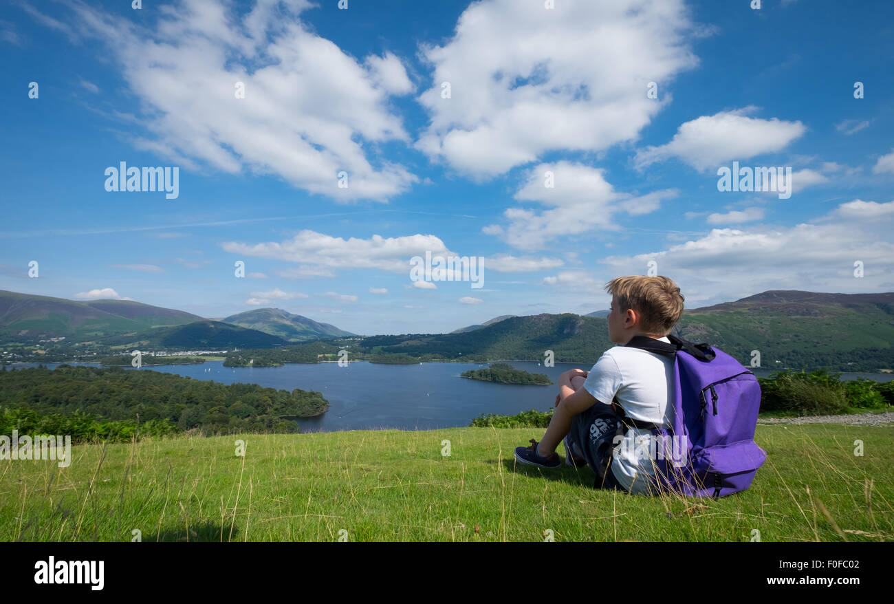 A boy stops to take in the view of Derwentwater in the Lake District from Catbells fell near Keswick, Cumbria, UK - Stock Image