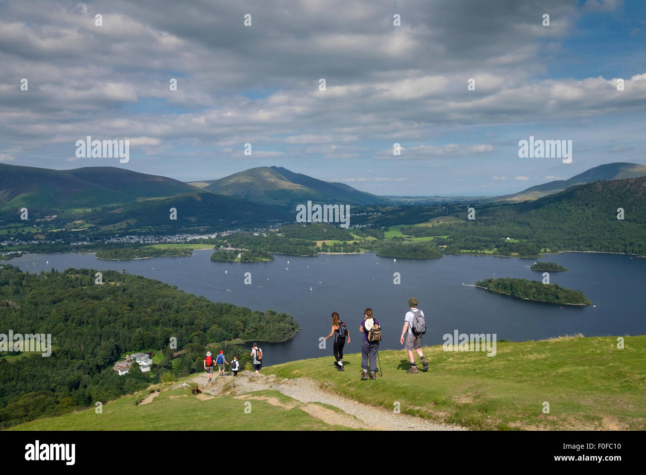 Trekkers take in the view of Derwentwater from Catbells fell near Keswick in the Lake District - Stock Image