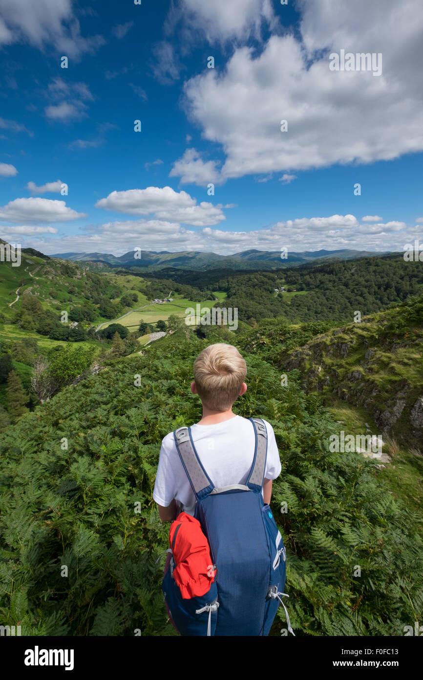 A teenage boy looks out across the horizon ready for an outdoors adventure in the Lake District, Cumbria, UK - Stock Image