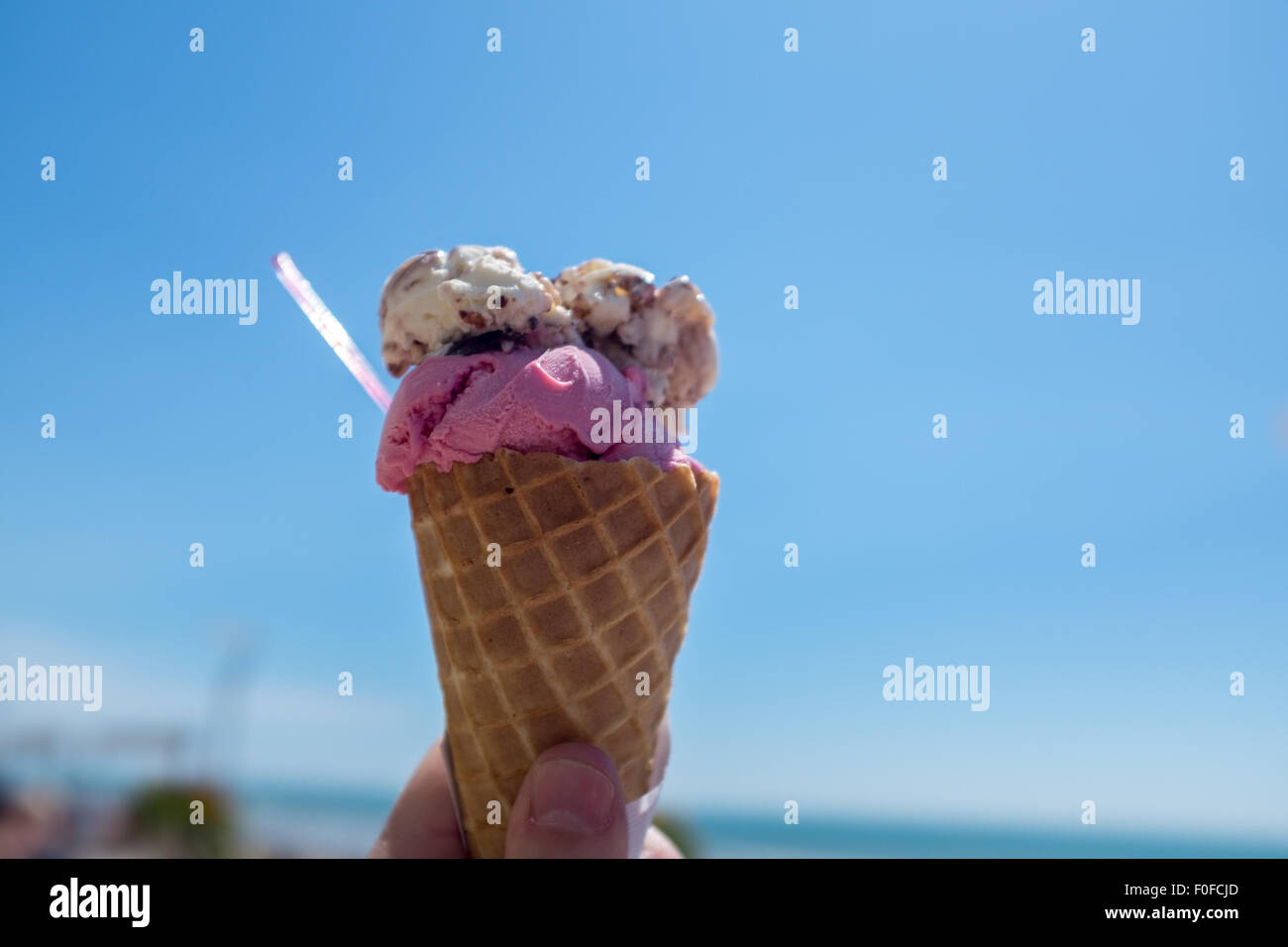 Ice cream cone against a bright clear blue summer sky - Stock Image