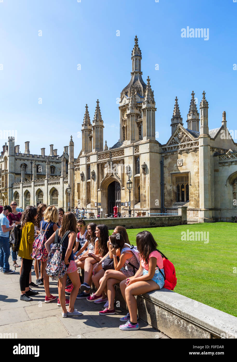 Young foreign students sitting outside King's College, King's Parade, Cambridge, Cambridgeshire, England, UK - Stock Image