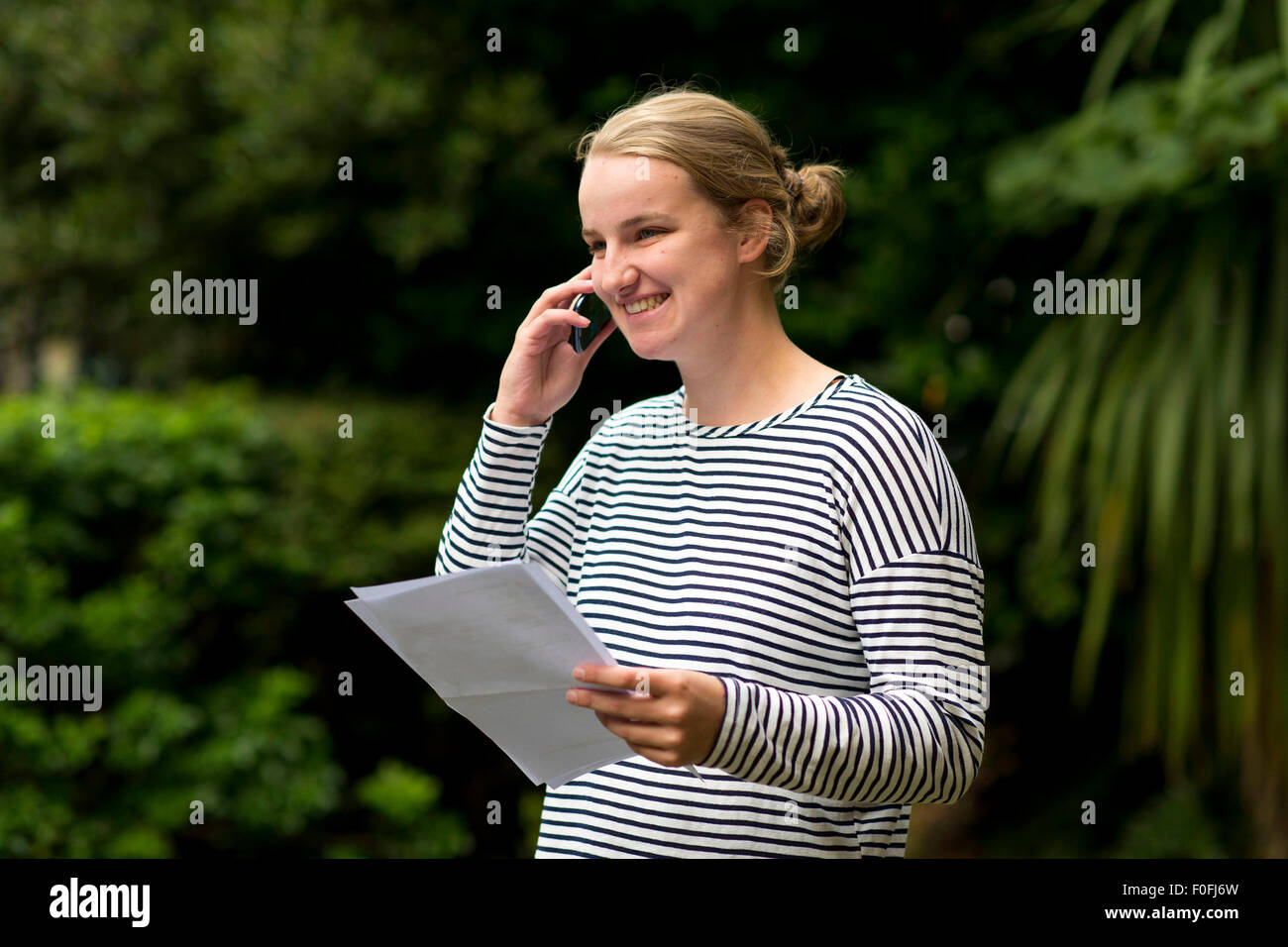 A blonde female GCSE student happy with her exam results. - Stock Image