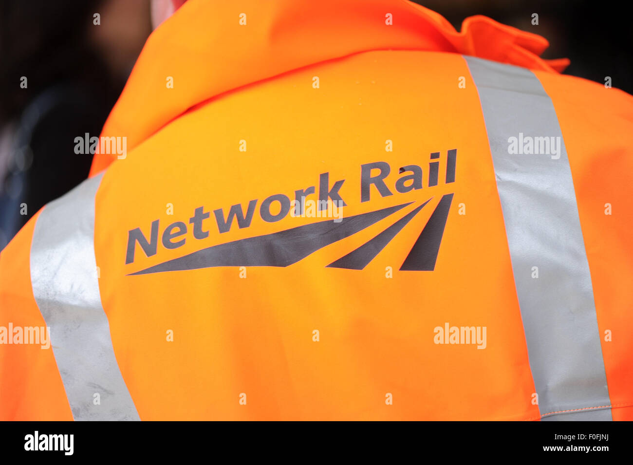 A Network Rail employee at a train station. - Stock Image