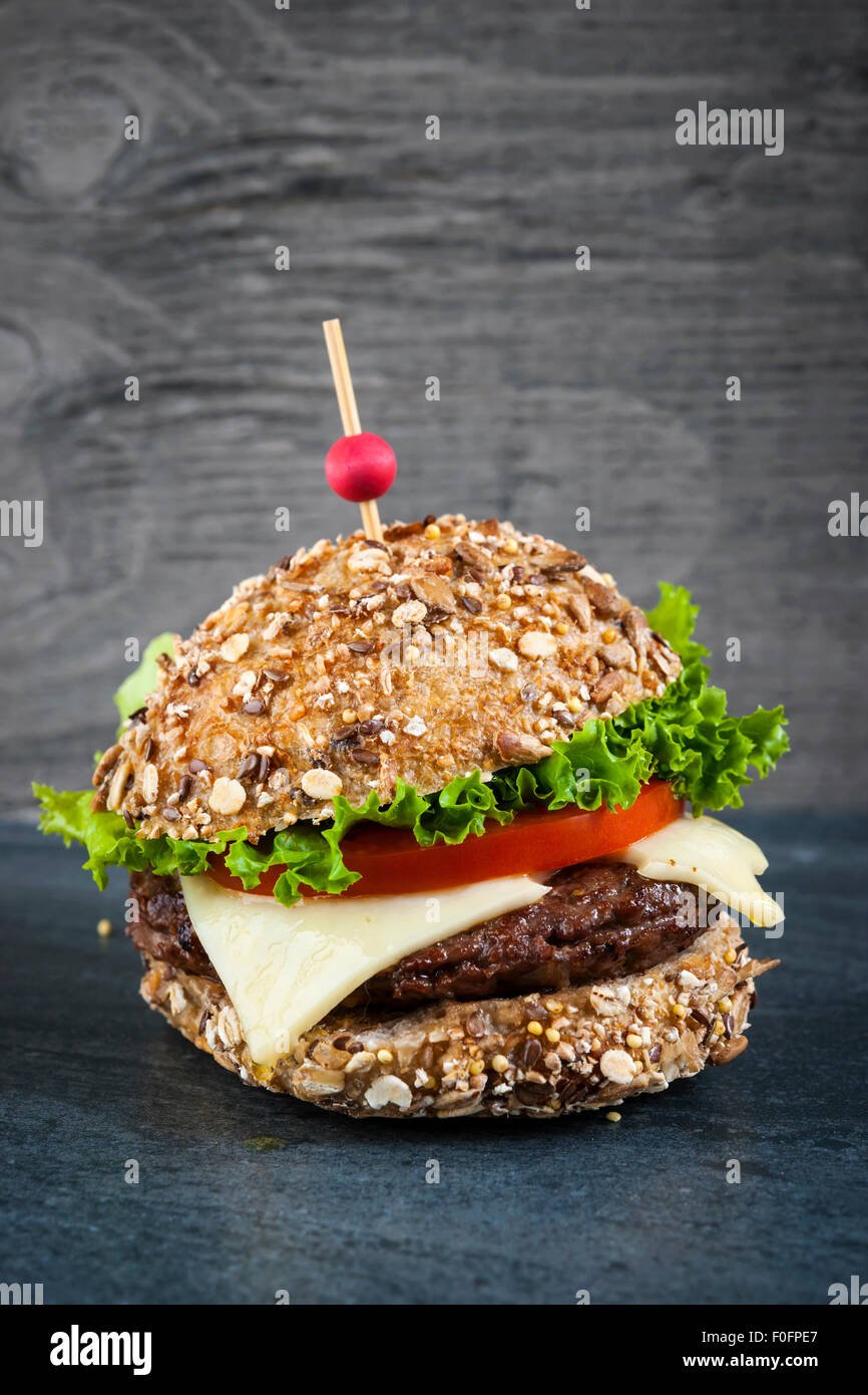 Gourmet hamburger with swiss cheese and fresh vegetables on multigrain bun over dark background Stock Photo