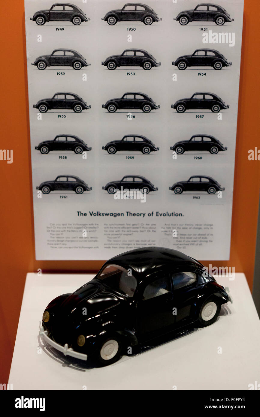 The Volkswagen Theory of Evolution poster and a VW Beetle model - Stock Image