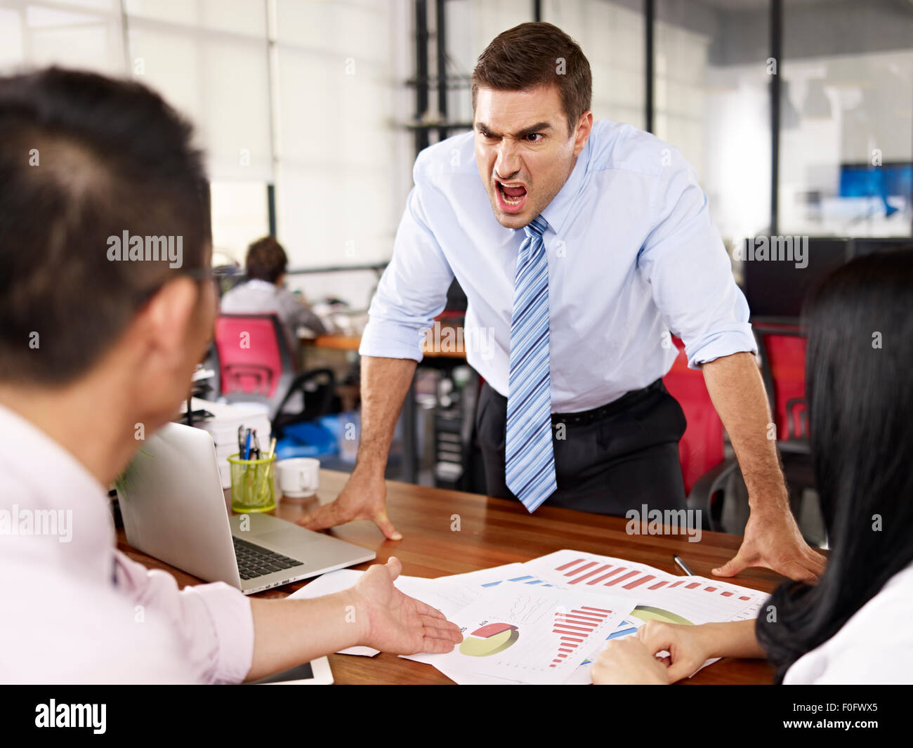 bad-tempered caucasian business executive yelling at two asian subordinates in office. - Stock Image