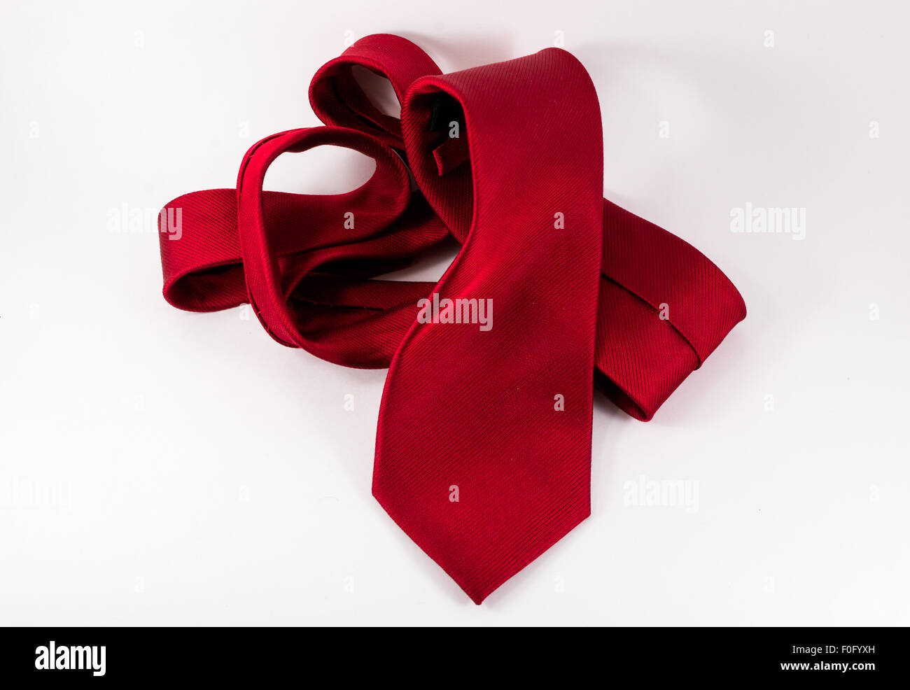 Single crumpled red silk tie belonging to a modern business man on a white horizontal background - Stock Image