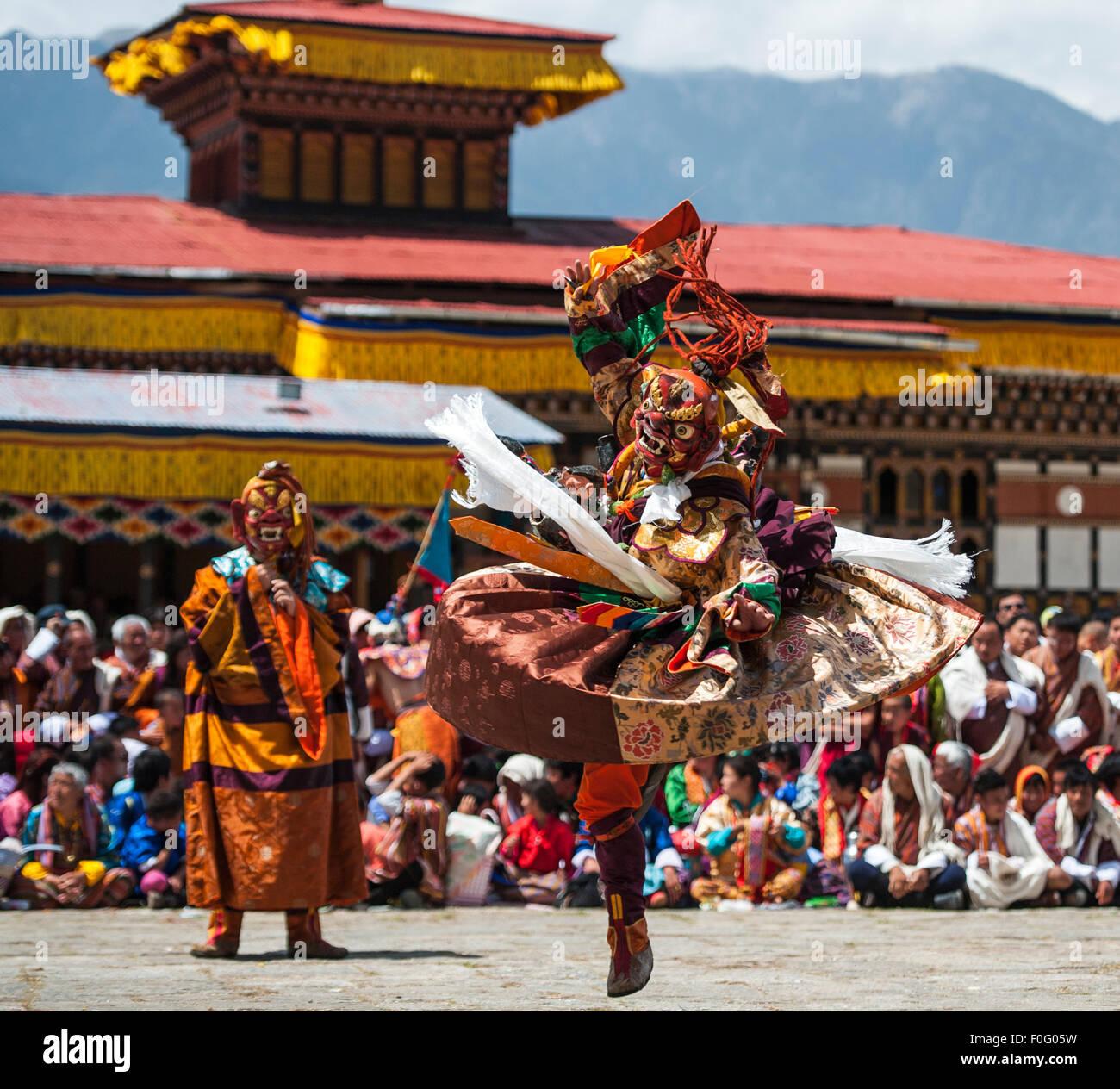 Dance of terrifying deities (Tungam) with spectators in the background Paro religious festival Bhutan - Stock Image