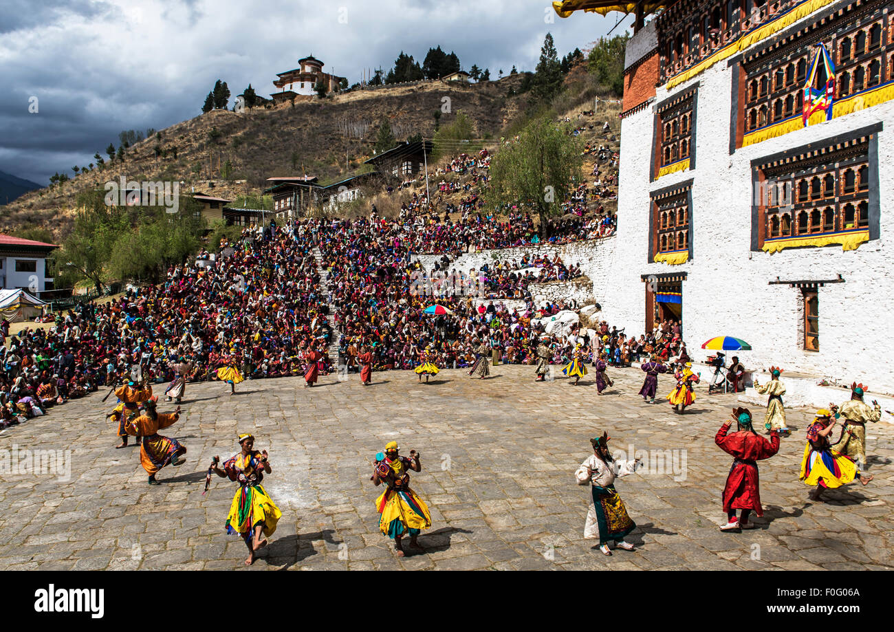Dancers performing with spectators and temple in the background Paro religious festival Bhutan - Stock Image