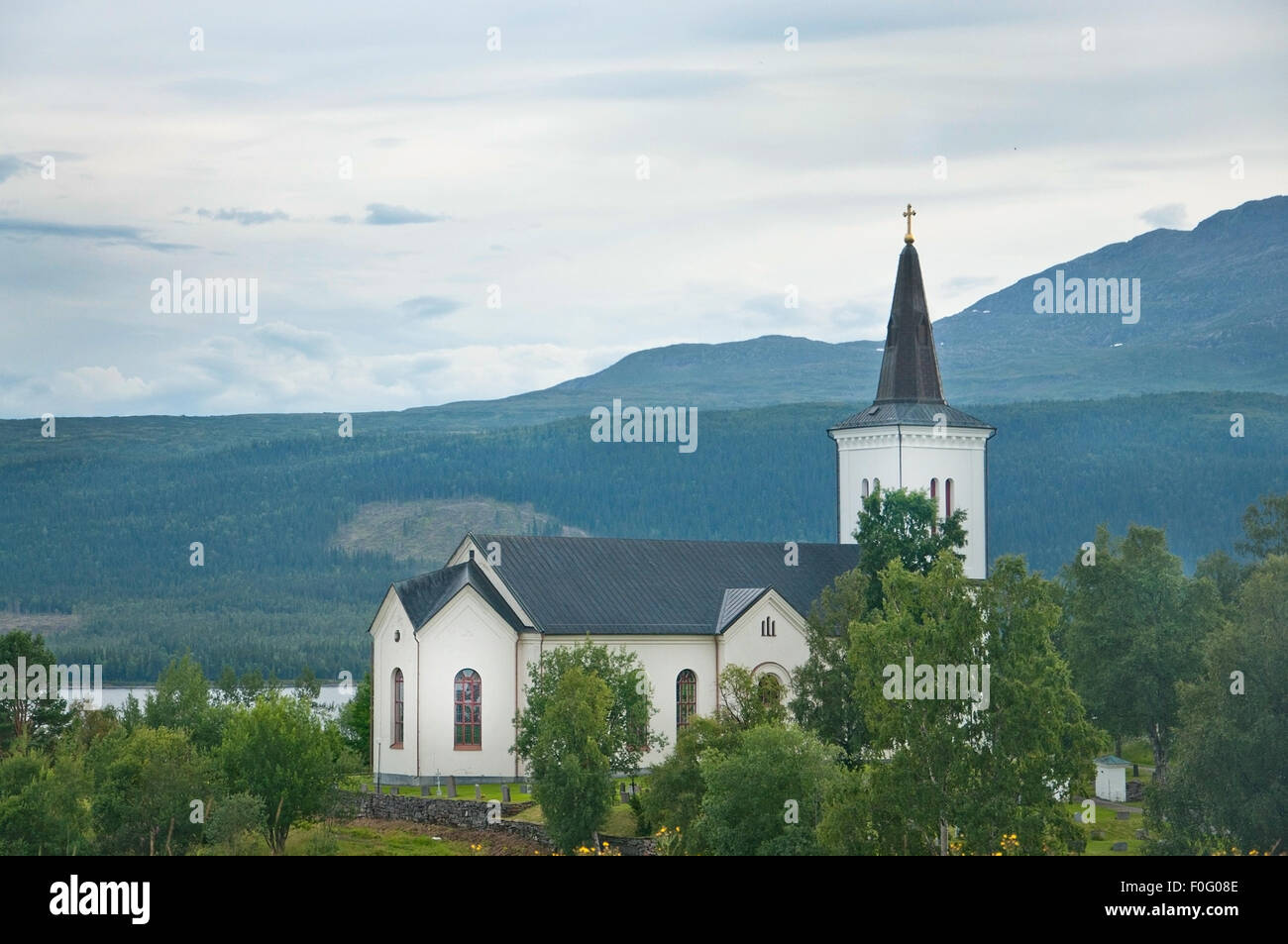 White church by lake  near Jarpen in Northern Sweden on an overcast day. - Stock Image