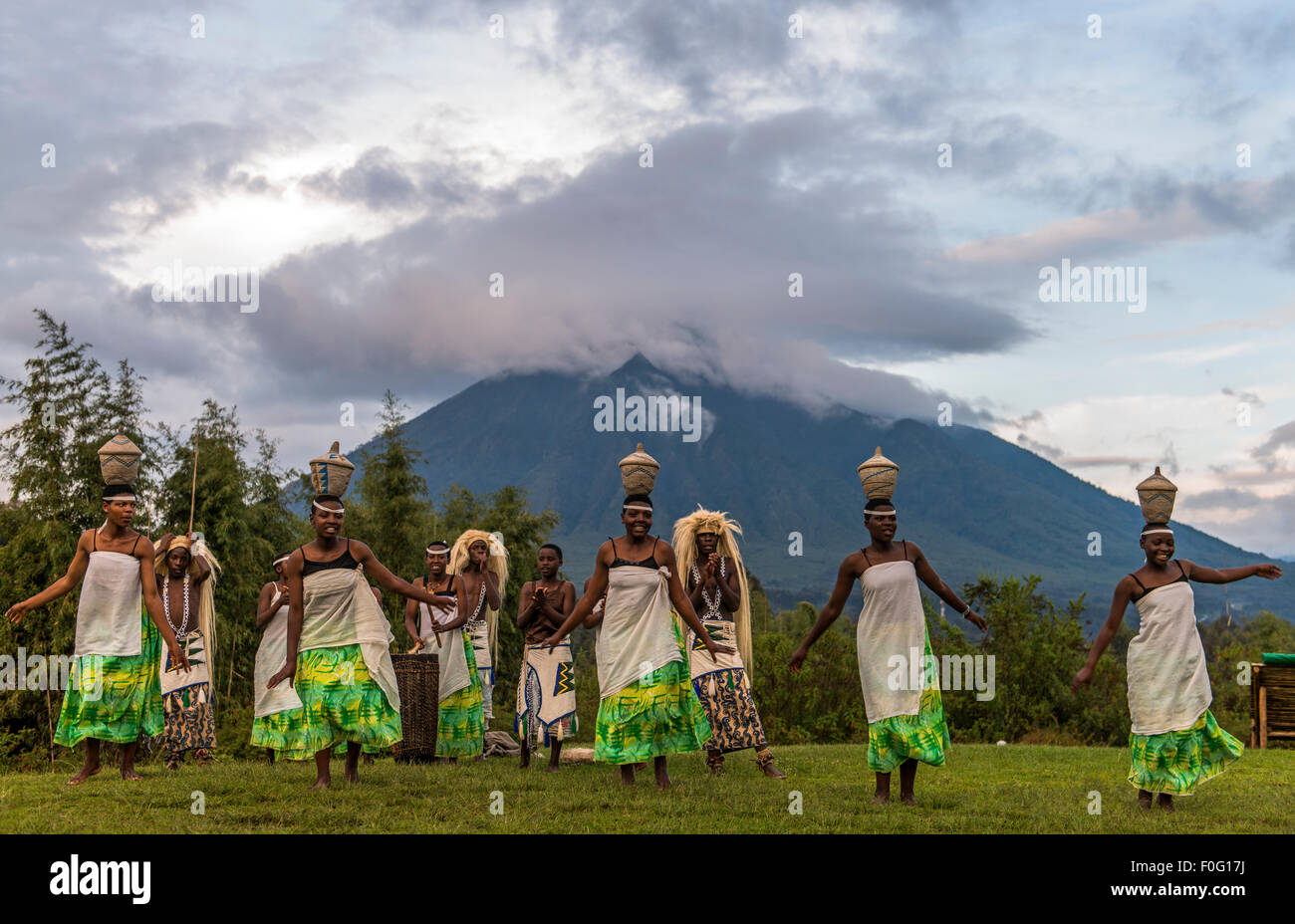 Local dancers performing a traditional dance with Virunga mountains in the background Volcanoes National Park Rwanda - Stock Image