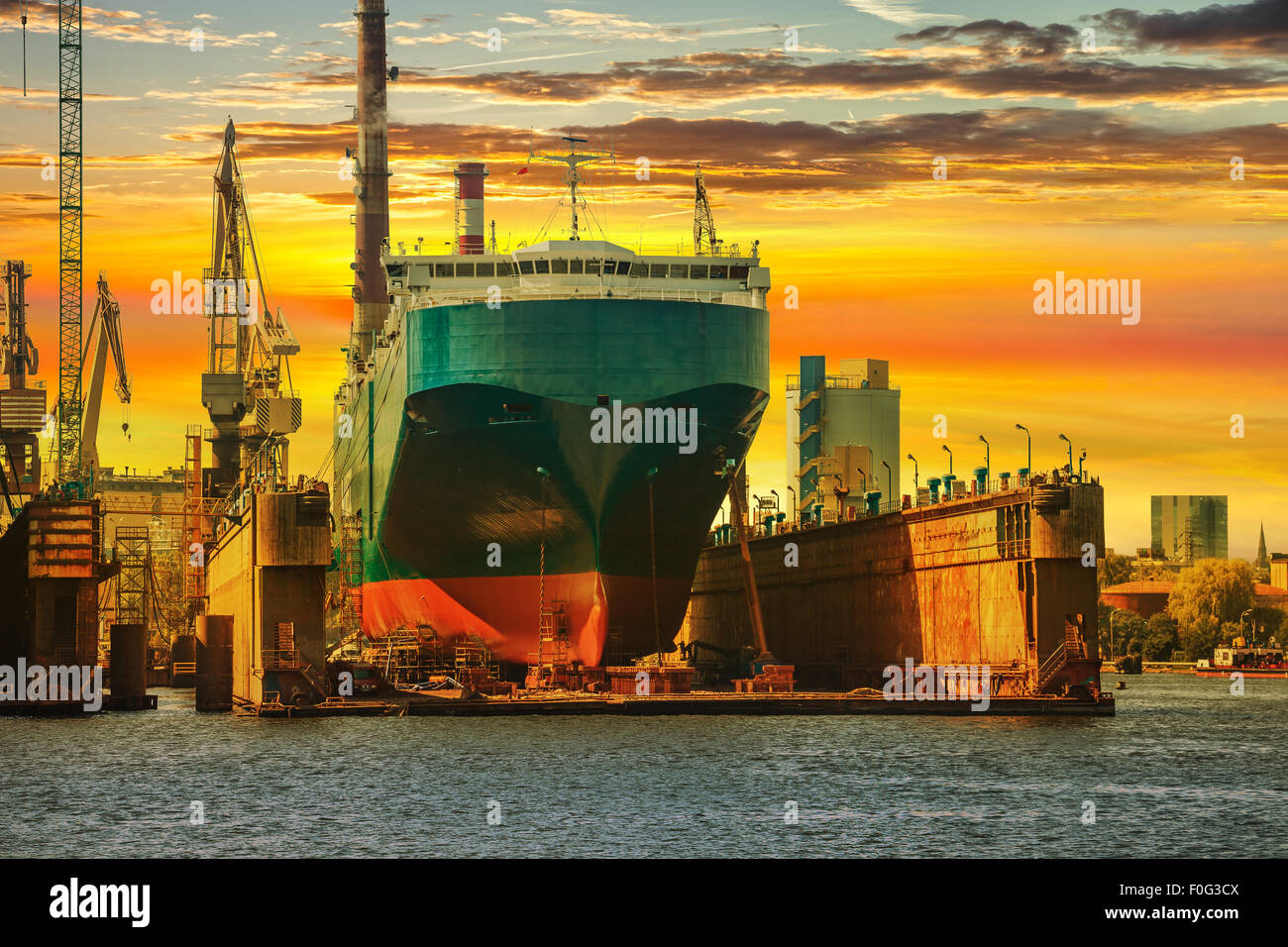 Ship being repaired in dry dock at sunset in Gdansk, Poland. Stock Photo