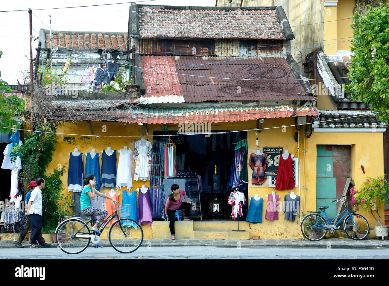 Woman cycling past clothing store, Hoi An, Vietnam - Stock Image