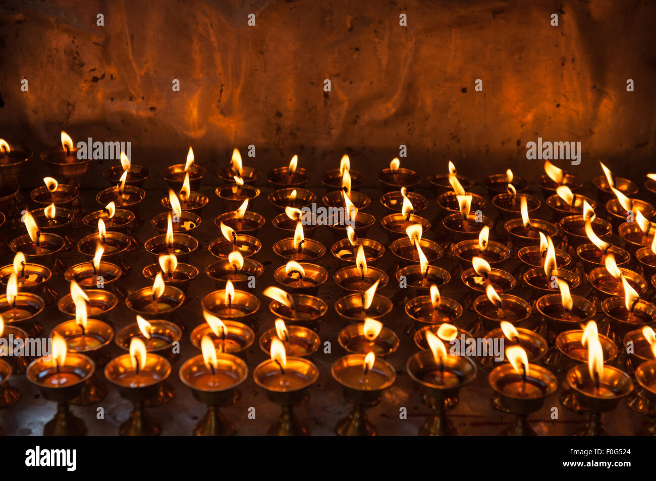 Dharamsala, Himachal Pradesh, India. Rows of burning butter lamps at the Buddhist temple in the Norbulingka Institute. - Stock Image