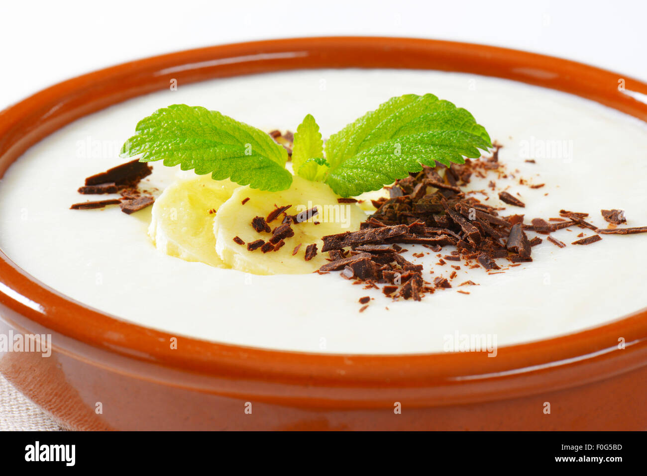 Bowl of smooth milk pudding with sliced banana and grated chocolate - Stock Image