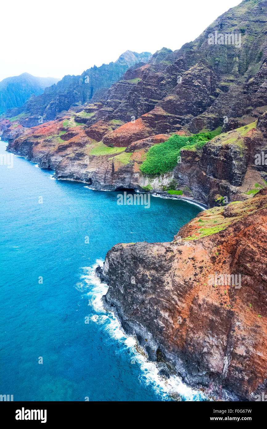 An aerial view of the Na Pali coast in Kauai Hawaii during a vibrant, sunny day shows the rich colors of the scenic - Stock Image