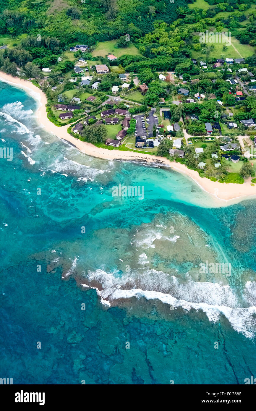 An aerial shot of the Kauai, Hawaii coastline showing the blue water and residential property which lines a small - Stock Image