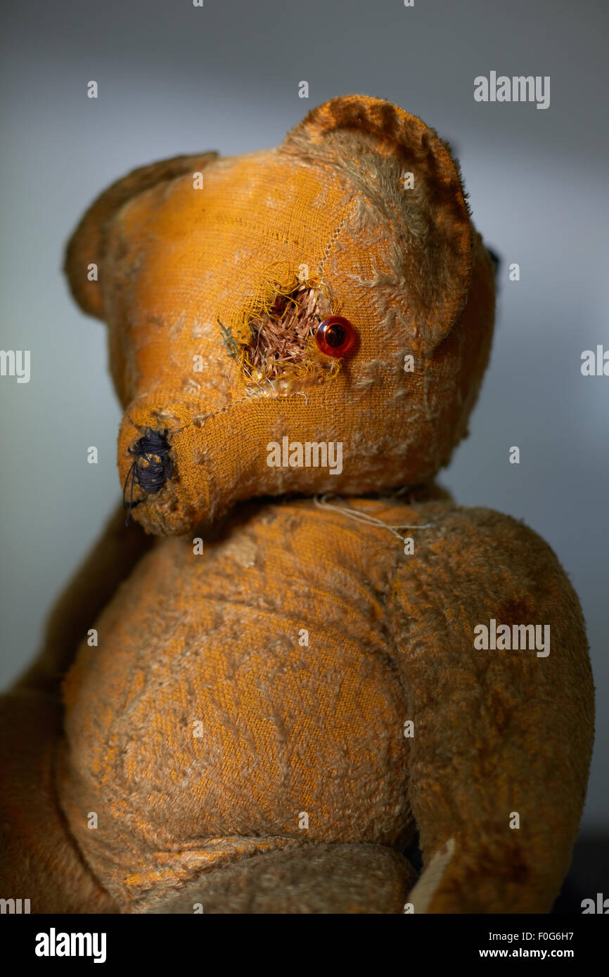 An old worn out teddy bear with damaged eye. - Stock Image