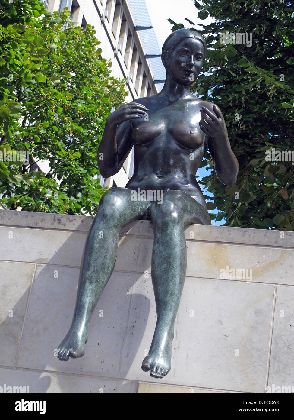 Three girls and a boy by Wilfried Fitzenreiter - Statue by the Spree River, Moabit, Berlin, Germany with building - Stock Image
