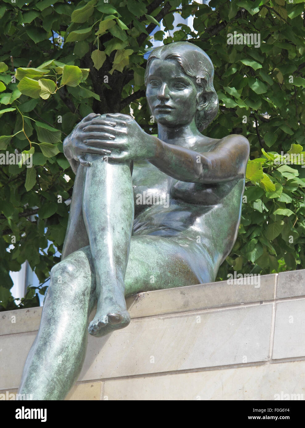 Three girls and a boy by Wilfried Fitzenreiter - Statue by the Spree River, Moabit, Berlin, Germany, reclining - Stock Image