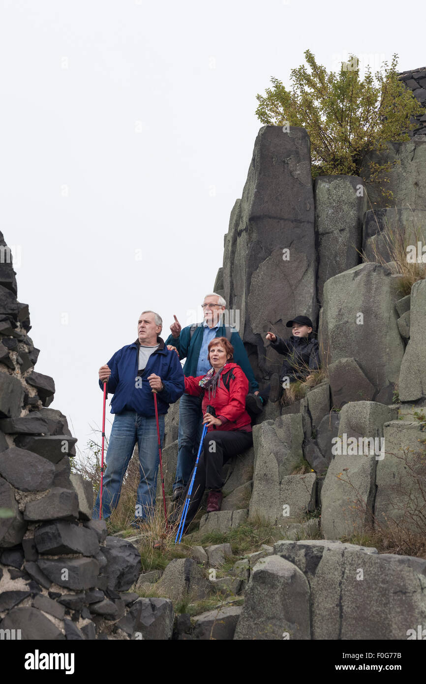 Three seniors with child boy pointing and hiking on rocky terrain. - Stock Image