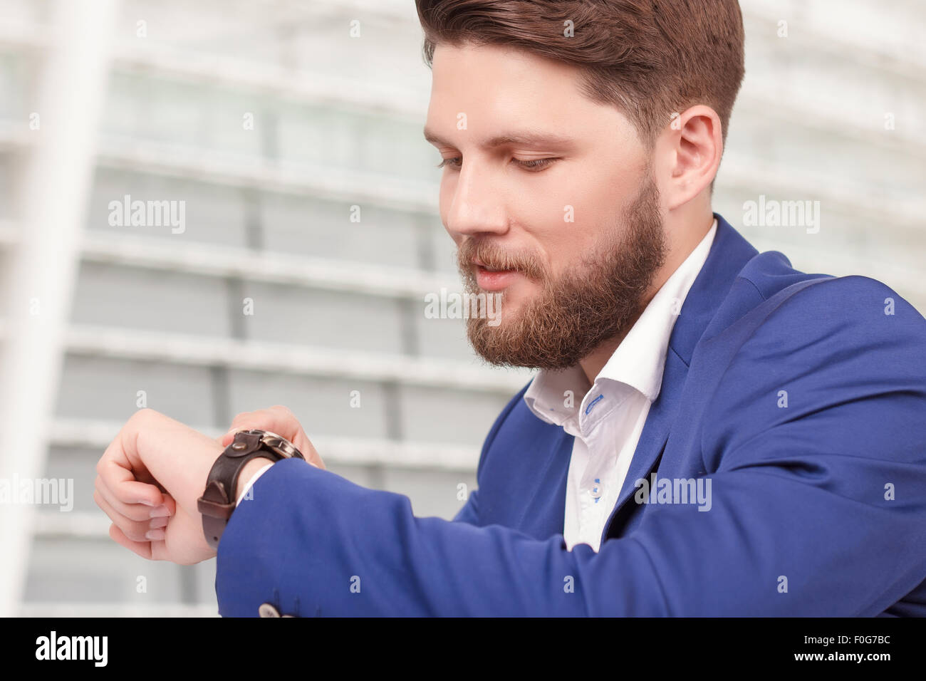 Handsome guy with beard checking time - Stock Image