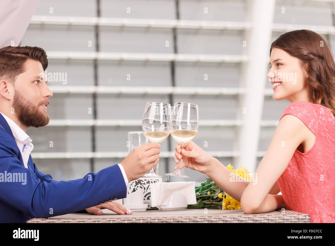 Young man and woman clinking glasses in cafe - Stock Image
