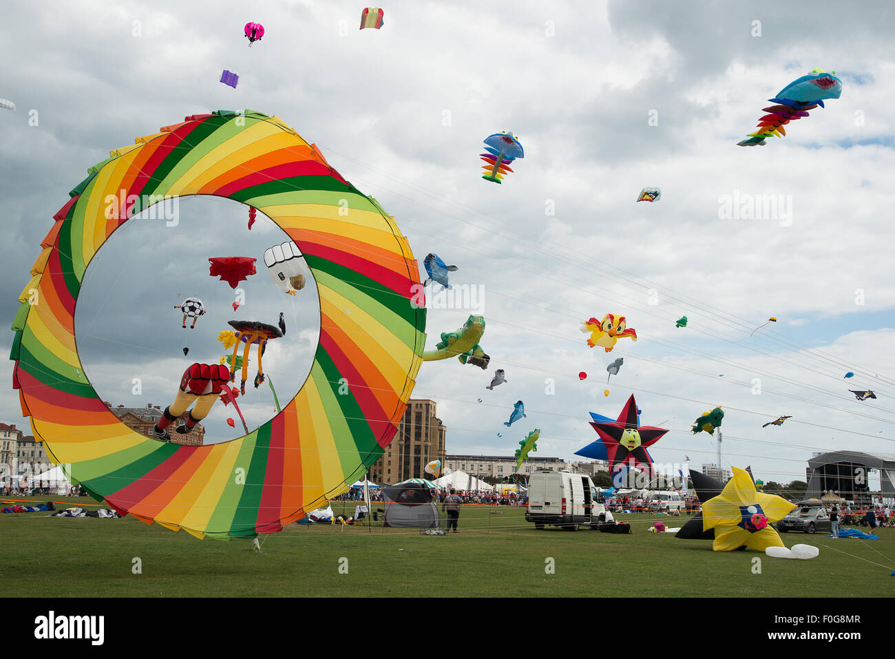 Portsmouth, UK. 15th August 2015. A huge rotating kite takes off with a multitude of kites flying in the background Stock Photo