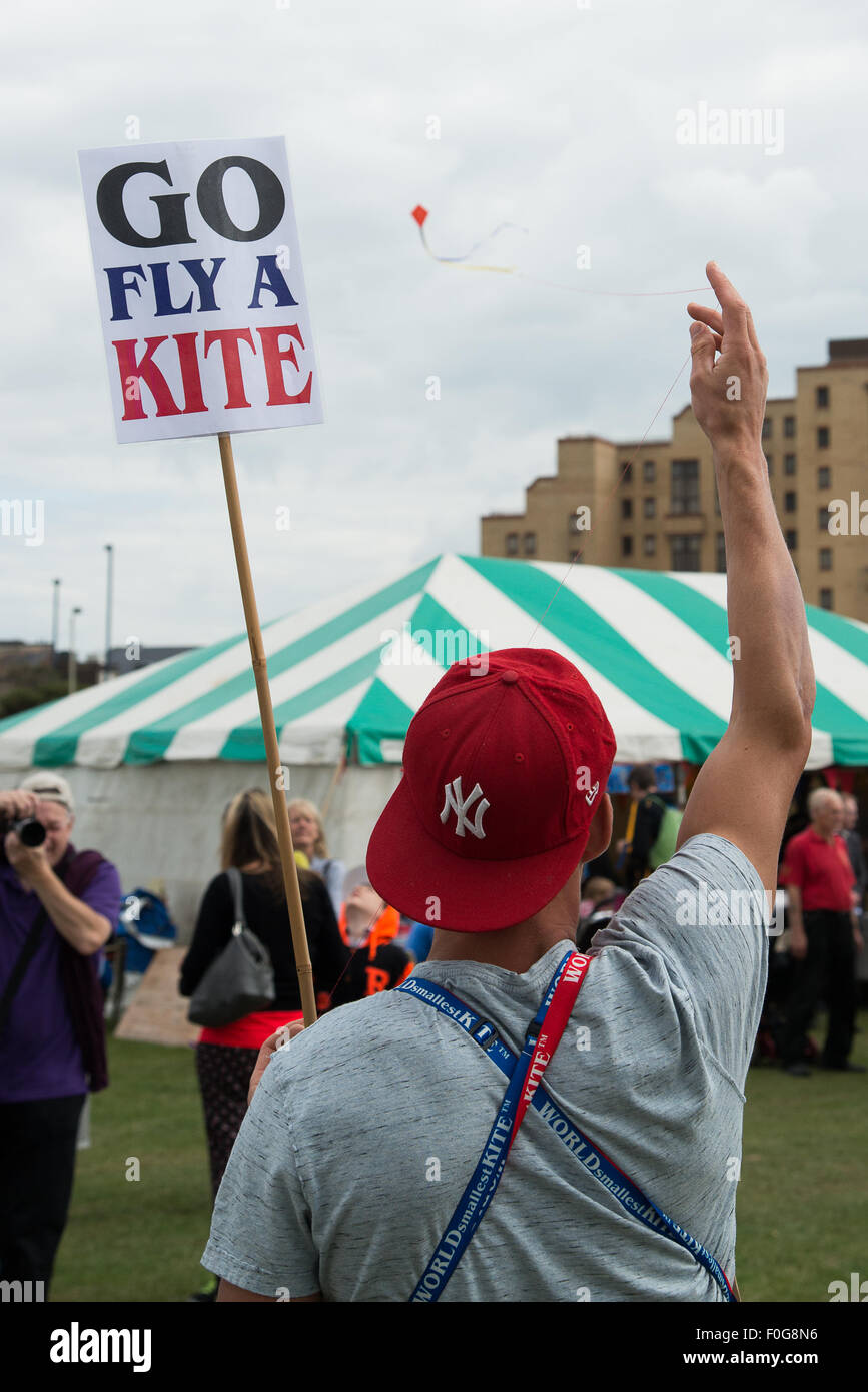 Portsmouth, UK. 15th August 2015. A kite seller demonstrates the worlds smallest kite as his photograph is taken Stock Photo