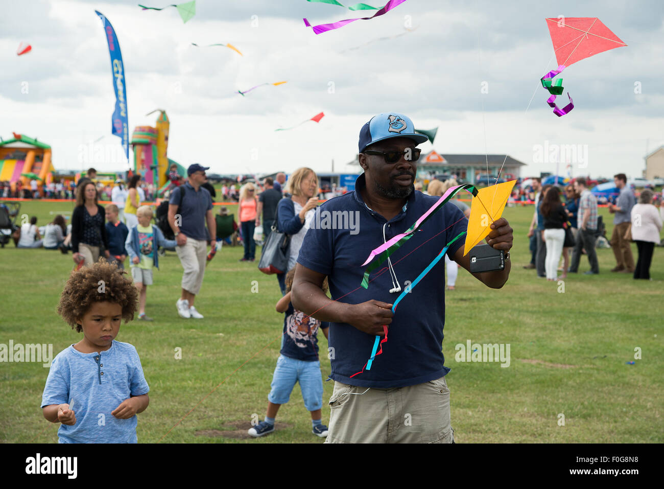 Portsmouth, UK. 15th August 2015. A man launches a string of kites as children look on at the International Kite Stock Photo